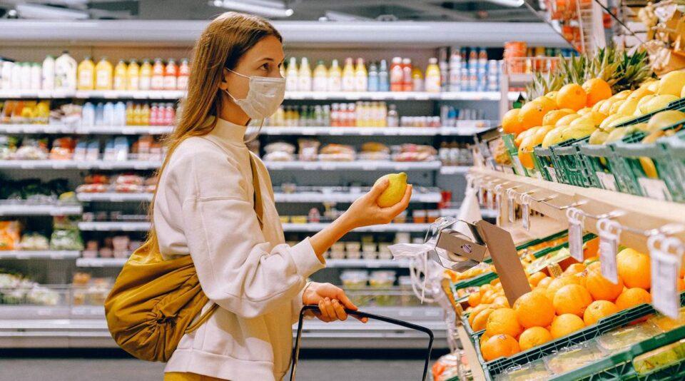 Жінка в масці купую продукти в магазині