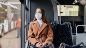 Жінка в масці їде в громадському транспорті